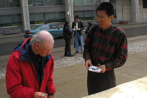 梁彪先生(右)在向路人讲述妈妈的故事(大纪元)