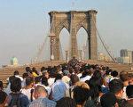 14日大停電﹐紐約布魯克林大橋附進塞滿了人群。(法新社)