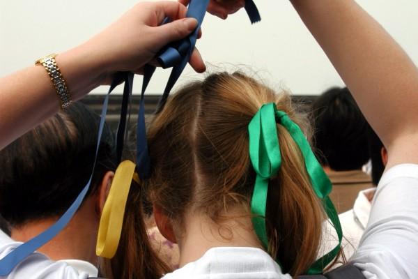 一名外籍女子把彩色丝带系在头发上,表达保护维港的决心。(大纪元记者摄)