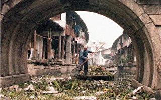 图为绍兴一名工人在河上清理工厂排放的垃圾。(法新社)