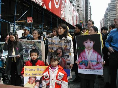 张玉辉的幼儿(左下角)在纽约手举父亲照片呼吁营救。(大纪元图片)