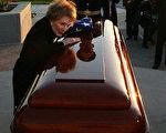 图为6月11日傍晚在夕阳余晖下泪流满面的里根遗孀南西伏在棺木上久久不能自已。(法新社)