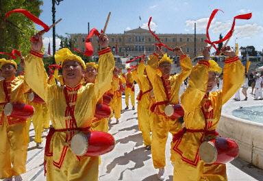 8月11日,約百名法輪功學員在希腊雅典舉行游行。據悉法輪功是奧運期間唯一被允許在雅典遊行的團體。圖為法輪功學員的腰鼓隊。(法新社圖片〕