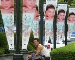 上海一男子坐在外国化妆品的广告牌下(LIU JIN/AFP/Getty Images)