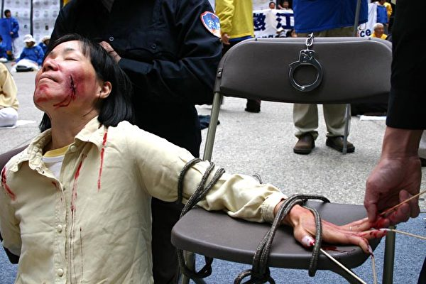 2004年5月,法輪功學員在美國芝加哥以真人、模型演示等形式再現江氏集團迫害法輪功學員的部份酷刑。慘烈的迫害震撼了芝加哥觀眾。圖為酷刑演示:手指釘竹籤。各種令人觸目驚心的酷刑用來逼迫法輪功修煉者放棄信仰。(大紀元資料圖片)