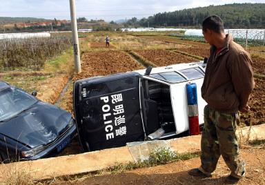 圖:因政府征地農民沒有領到當局該付的款項,11月3日昆明附近的農民與警察發生衝突,把九輛警車推翻在田裡。(法新社)   <p><figcaption class=