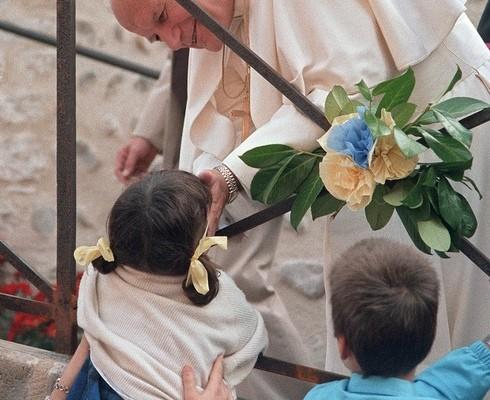 亲民的教宗,接受小孩的献花((图片来源:AFP/Getty Images,摄于1987年)
