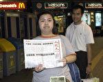 市民索閱香港《大紀元時報》後,高興地讓記者拍照。(大紀元)