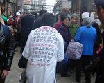 图:北京信访办门口等待上访的民众,一上访者背上写满对官员腐败的声讨檄文(大纪元)