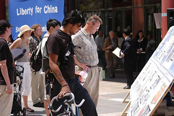 路过的人在观看图片资料(大纪元)