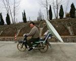 安徽一农民用摩托车驮著卫星天线。(Getty Images)