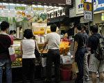 炎熱天氣為街頭小食店帶來更多顧客,市民和遊客停下腳步購買飲料如果汁等解渴。(大紀元)