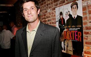 麦可•史怀特参加《巴克斯特》纽约首映会后,于电影海报旁留影/Getty Images