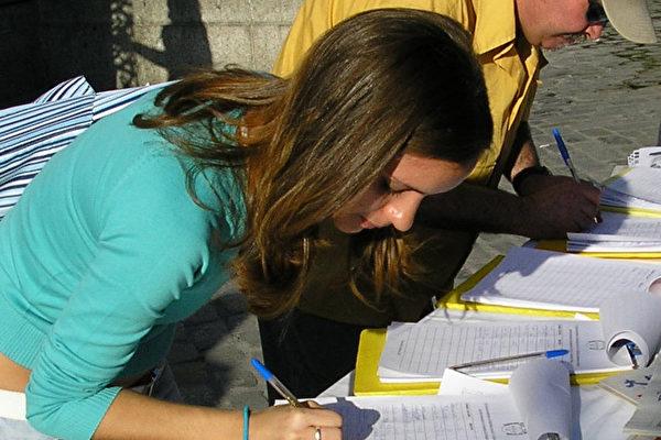 这名女孩在看了揭露中共暴行的图片后流着泪在声援表上签上了自己的名字(大纪元)