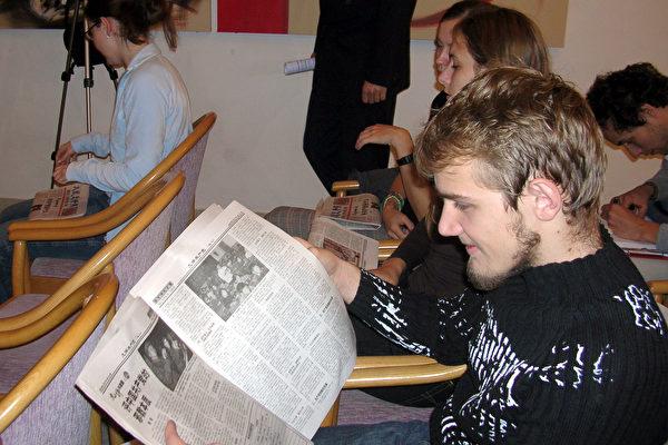 在国际关系大学内学习中文和中国历史的学生每人拿了一份中文的9评报纸。
