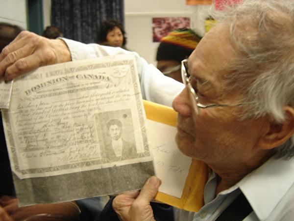 图:多伦多居民Tom Lee手持加拿大政府1918年7月5日发给他父亲Billy Lee征收人头税的证书。(大纪元)