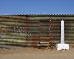 圖為美墨邊境的一段圍牆和一個界碑。(OMAR TORRES/AFP/Getty Images)
