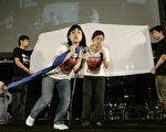 """香港天安门母亲运动表演""""玫瑰的呼唤""""街头剧,谴责中共对在""""六四""""屠城中失去亲人的天安门母亲的迫害,17年来无日无之。她们强烈要求让她们自由悼念遭屠杀的家人。图为其中一幕,中间持蓝布者为天安门母亲,她想悼念亲人但遭左下方代表中共的人所阻挠。站在蓝布母亲后面的人演绎年纪老迈、体弱多病的天安门母亲,过了这17年的光阴里,已时日无多,渴望有生之年能够争取到自由悼念亲人的权利。(大纪元记者吴琏宥摄)"""