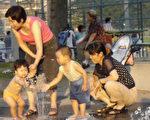 8月1日多伦多华人聚居的北约克区喷水花园前小孩在戏水避暑。(大纪元)