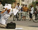 图为2006年8月31日,一位民众拿着文件在北京第二中级法院外表达心中不满(PETER PARKS/AFP/Getty Images)