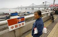 一名中国妇女在鸭绿江畔的中朝边境遥望桥对岸的朝鲜。10月9日法新社照片