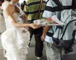 一名穿上婚紗的少女正在會場附近派發有關博覽會的宣傳單張。(TED ALJIBE/AFP/Getty Images)