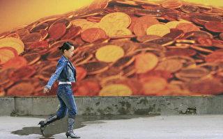 2006年10月19日﹐北京。一名妇女经过一个印有钱币的广告牌。(FREDERIC J. BROWN/AFP/Getty Images)