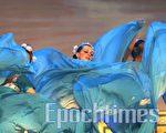 """小桥在《八仙过海》波涛中偶露面孔。舞蹈开场,十八位舞者以柔美的舞姿快速舞动优雅的蓝色长裙,翻起""""海浪""""阵阵。巨大的舞台背景上,蓝天白云映衬著碧波粼粼的蓝色大海,天高水阔。蓬莱山仙境,层峦迭障的山峰时隐时现于变幻的云海之中,流动着的瀑布仿佛自天而降,奇景虚幻缥缈,美不胜收。海浪前飘来前来渡海的八位仙人,各携""""宝器""""翩至登场。(大纪元)"""