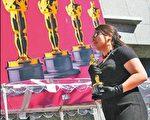 女学生战战兢兢护送小金人进柯达剧院。(图片/法新社)