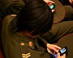 中共两会期间,与会代表非常优闲的玩起游戏机。(图:新唐人电视台)