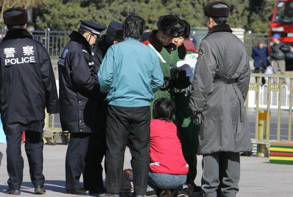 美国公民察尔斯‧蔡因回国去看望居住在湖南长沙的八旬母亲,而遭到中共国安骚扰及非法绑架。图为2007年3月7日, 在北京天安门广场警察正在盘问一位妇女。(Photo credit should read FREDERIC J. BROWN/AFP/Getty Images)
