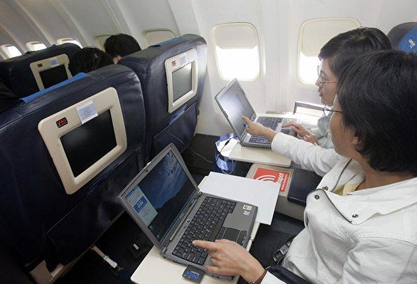 在狭窄的机舱内很难避开邻座的电脑萤幕(STR/AFP/Getty Images)