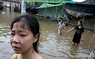今年7月重庆暴雨成灾,一位哭泣的小女孩在试图穿过又一次被暴风雨袭击后的街道(AFP)