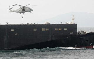 """由美军大型货物运输船扮演,假设载运大规模杀伤性武器相关物资被发现,日本海上自卫队出动""""雷""""号驱逐舰阻止。(KAZUHIRO NOGI/AFP/Getty Images)"""