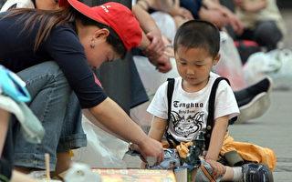 尊老爱幼是中华民族的传统美德,图为一名年轻的妈妈陪儿子玩游戏。(TEH ENG KOON/AFP/Getty Images)