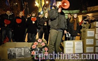 烏克蘭青年組織代表在紙做棺材和牆壁前發言。(攝影:Vladimir borodin/大紀元)