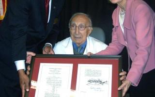 參議員哈奇森(右)(Kay Bailey HUTCHISON)與眾議員艾爾格林(左) (Al Green)頒給狄貝奇醫師(中)(DR. MICHAEL E. DEBAKEY)鑲嵌有國會議案副 本的金質獎章。(圖片由Al Green office提供)