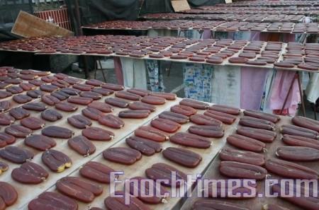 乌鱼子制作中,现在是渔民捕乌鱼的时候,乌鱼子也是年节送礼的大热门,所以鱼市上现在很多人卖乌鱼子、乌鱼腱。(摄影:苏柏兴/大纪元)