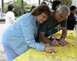 芭芭拉与丈夫吉米.科尔图,在人权圣火的布条上签名,以行动表示支持。(摄影﹕林家维/大纪元)