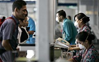 在流感季節,馬來西亞航空公司(Malaysia Airlines)工作人員在機場面戴口罩預防感染 (TENGKU BAHAR/AFP/Getty Images)