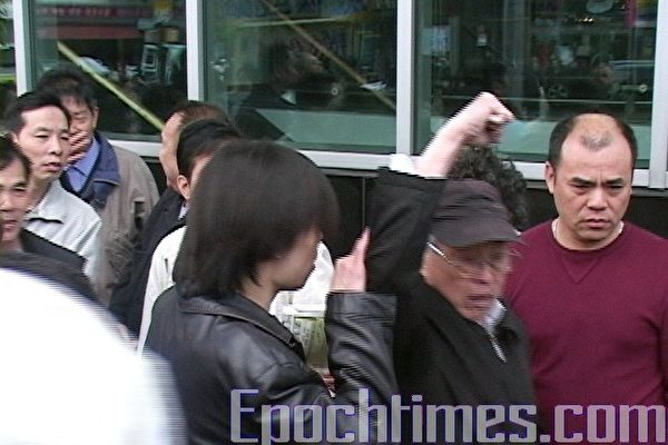 這位頭戴黑帽的人,罵著非常難聽的話,還舉起拳頭威脅要打人和砸攝影人員的相機。(大紀元圖片)