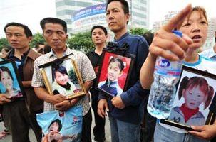 四川德阳地震中失去子女的愤怒的家长们手持孩子的遗像,到市政府抗议(法新社)