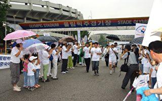 圖說:7月2日,由「法輪功受迫害真相聯合調查團」(簡稱CIPFG)發起的「人權聖火全球傳遞」活動來到韓國,圖為「人權聖火」傳遞活動在首爾奧林匹克主競技場(綜合運動場)前出發,各界民眾冒雨前來加油祝威。(金國煥/大紀元)