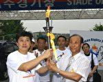 """环保活动家、数学院院长金昌铉,是韩国第一位拒绝传递北京奥运火炬的韩国人,在当天的""""人权圣火""""传递中,他又是第一位火炬手。图为7月2日,金昌铉(左)从CIPFD韩国副团长郑求辰手中第一个接过人权圣火主火炬。(金国焕/大纪元)"""