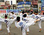 """全球""""人权圣火""""传递活动于当地时间7月5日抵达天安市,为庆祝""""人权圣火""""的到来,当地""""鸳鸯跆拳道训练馆""""的20多名跆拳道选手登台表演。(金国焕/大纪元)"""