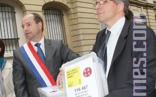 議員Jean-Jacques Urvoas(左)與國際大赦法國分部秘書長Stephan Oberreit攜11萬簽名抵達中共使館。(攝影:章樂/大紀元)