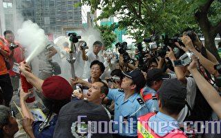 滅火筒未噴中聖火,卻噴到在旁採訪的記者。再噴。藍色的軍裝警員搶火炬,把火炬按到滅火筒的方向。(攝影:潘璟橋/大紀元)
