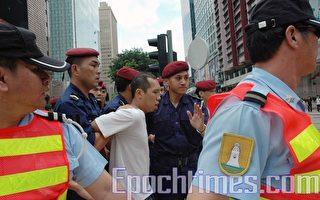 雖然利建潤並沒有反抗,但警方人員仍一直以這種反扣雙手的暴力方式帶走他。(攝影:潘璟橋/大紀元)