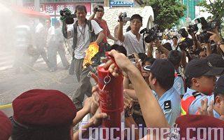 警員企圖用滅火筒噴熄人權聖火火炬(攝影:潘璟橋/大紀元)