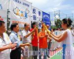 手持聖火的希臘女神將全球傳遞的聖火傳給香港的火炬手司徒華。(攝影:李忠原/大紀元)